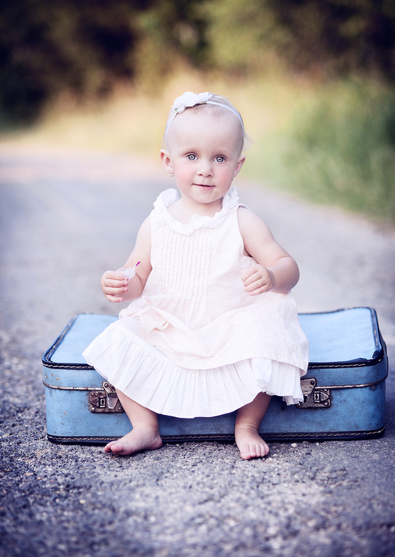 Baby sitting on a suitcase